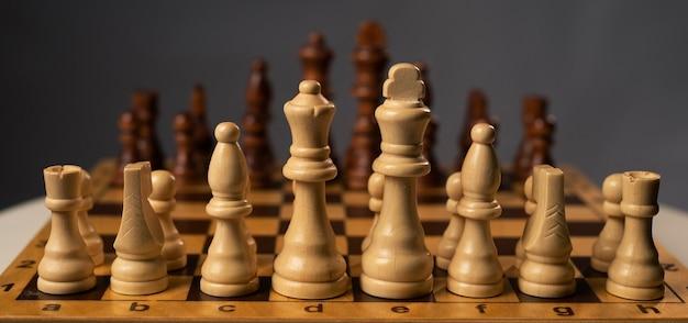 Шахматная доска с шахматными фигурами на сером столе.