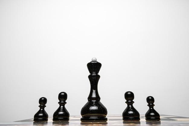 Шахматная доска с деревянными фигурами на сером фоне