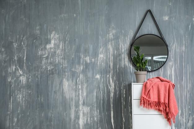 鏡付き壁の近くの箪笥