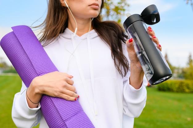 흰색 후드티를 입은 낚시를 좋아하는 소녀의 가슴은 보라색 매트, 물 한 병, 운동 후 헤드폰 착용, 야외 피트니스 운동