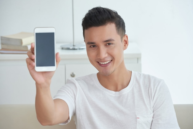 Chest up shot of asian guy showing a screen of his smartphone and smiling