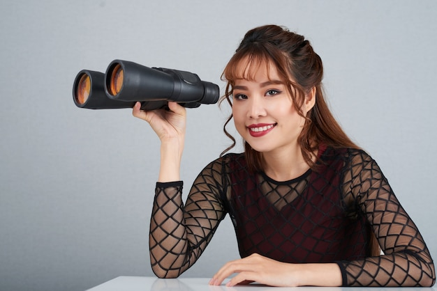 Chest up shot of cheerful woman holding the binoculars looking at camera