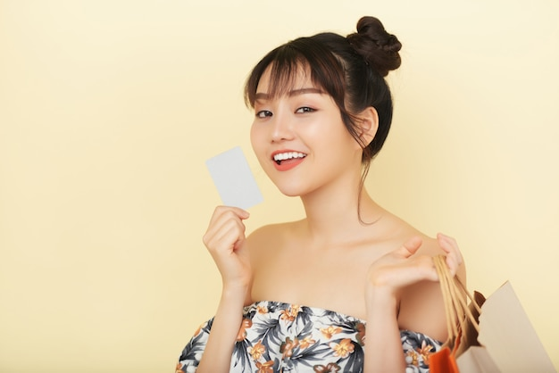 Chest up shot of young woman holding a bank card with shopping bags in her another hand