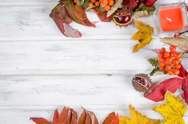 Chestnut and autumnal  leaves on the wooden background