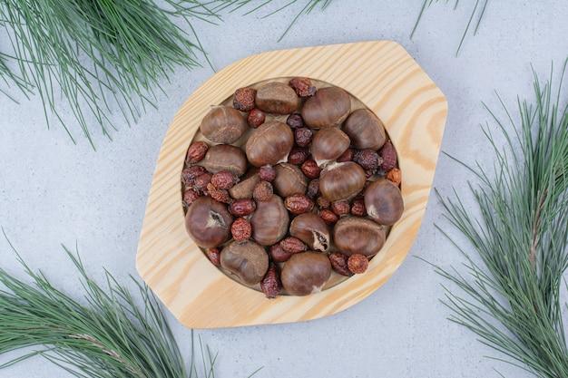栗と木のプレート上の乾燥ローズヒップ。