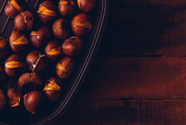 Chestnuts in a bowl flat lay on a dark wooden table