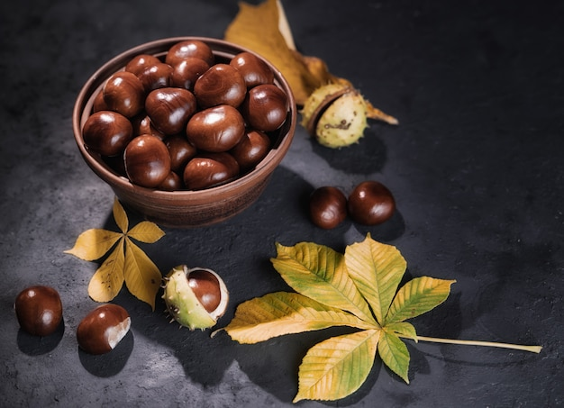 Chestnuts castanas in clay bowl on black background.