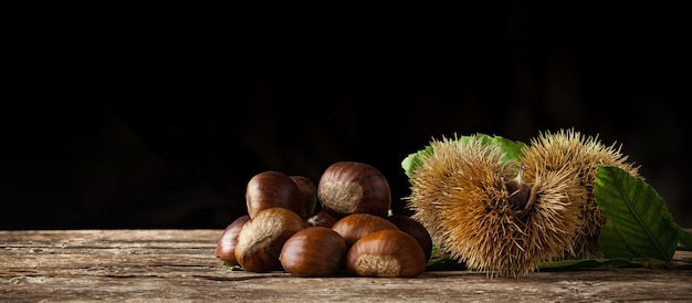 Chestnuts and chestnut bur on wooden table