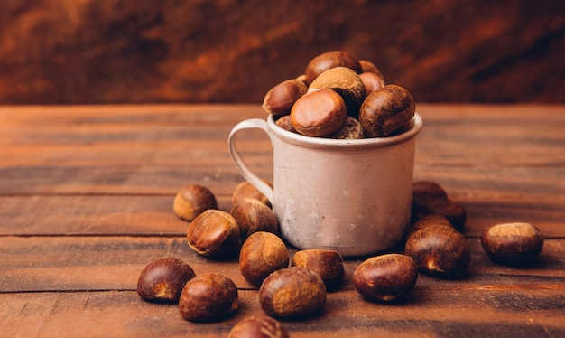 Chestnuts in a cup and around on a dark wooden table