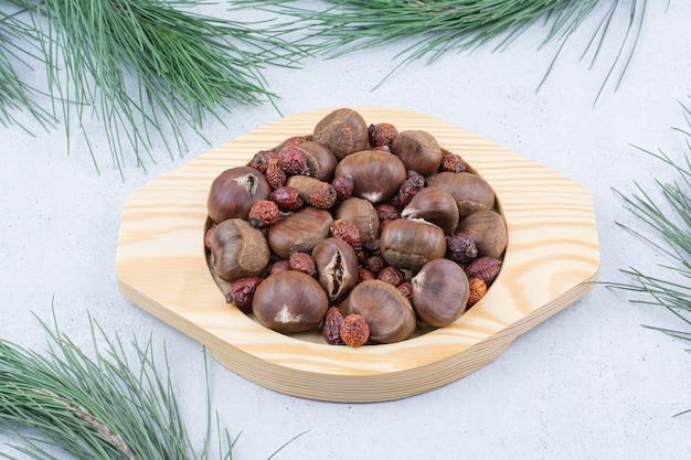 Castagne e cinorrodi secchi sul piatto di legno.