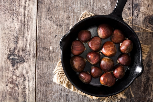 Chestnuts in iron pan on wooden table top view copy space