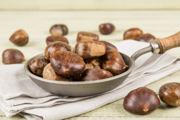 Chestnuts in a pan on a wooden.