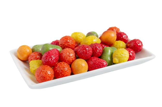 Chewing colorful gum in the form of fruit on a plate isolated on white background. close up