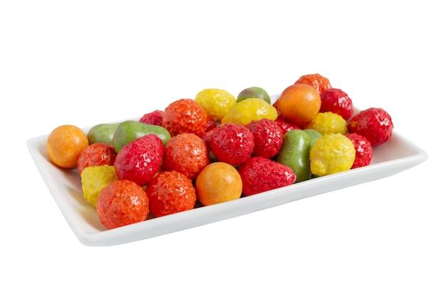 白い背景で隔離のプレートにフルーツの形でカラフルなガムを噛む。閉じる