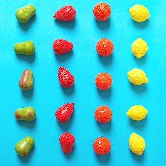 Chewing gum in the form of pear, orange, strawberry and lemon on a blue background are laid out in rows. bright fruit candy top view.