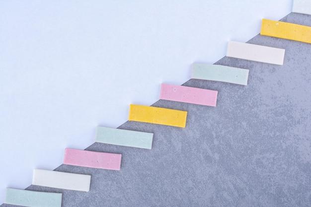 Жевательные резинки расположены по диагонали на белой / мраморной поверхности.