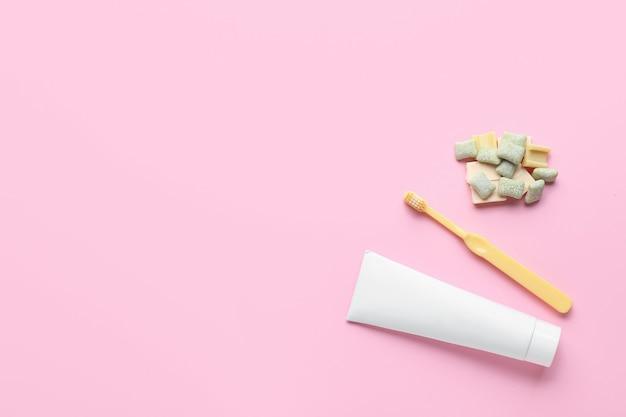 Жевательная резинка, зубная щетка и паста на цветном фоне