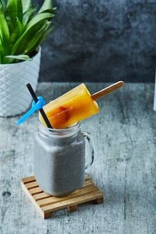 Chia milkshake with ice-cream and straw on the marble surface