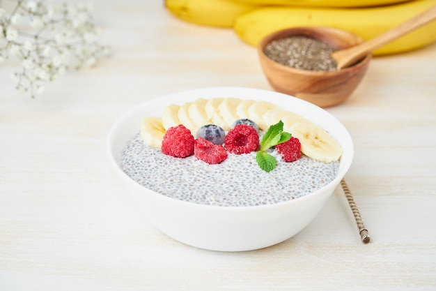 Chia pudding in bowl with fresh berries raspberries, blueberries. side view, white wooden