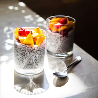 Chia pudding on coconut milk with raspberries and peach in glass jars