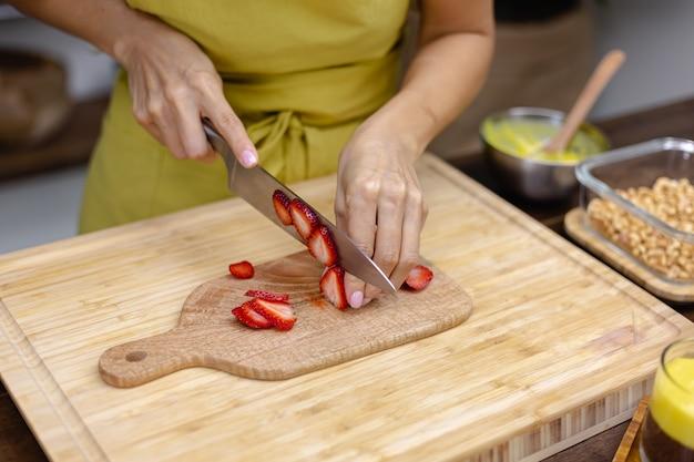 Chia pudding making process. woman cut strawberry on wooden board.