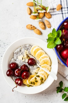 Chia pudding with banana, cherry and nuts in white plate.