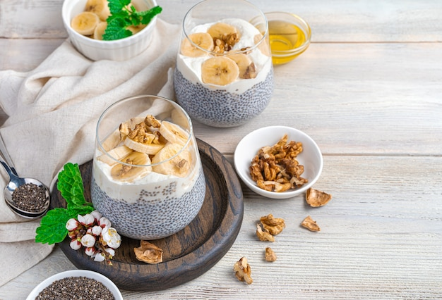 Chia pudding with banana, nuts and honey on a beige wall with space to copy. a healthy, vitamin-rich breakfast. the concept of diet and healthy eating.