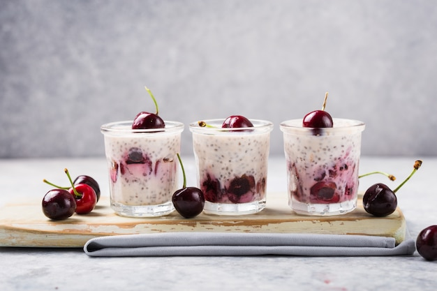 Chia pudding with cherry in a glass on a grey surface