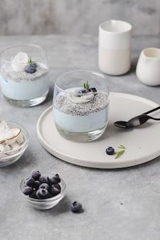 코코넛 밀크, 라즈베리, 로즈마리, 코코넛 칩, 블루 스피루리나를 곁들인 치아 푸딩