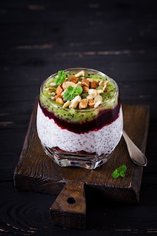 Chia pudding with fresh berries, nuts and mint in glass