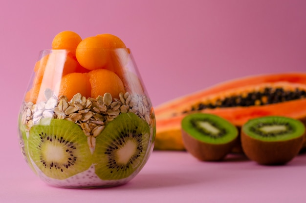Chia pudding with kiwi fruit, oatmeals and papaya balls in a glass on purple