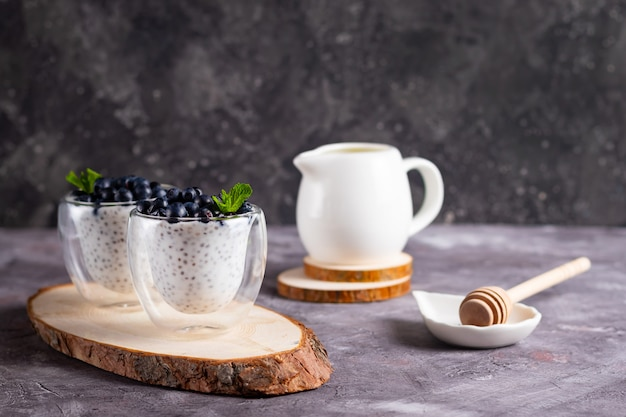 Chia pudding with mint and blueberries in glasses on a wooden stand with a honey stick