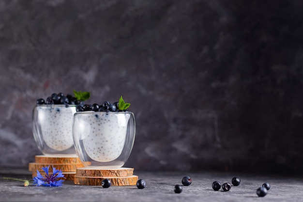 Chia pudding with mint and blueberries in glasses on a wooden stand