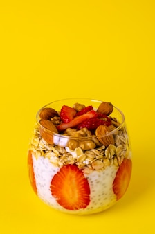 Chia pudding with strawberries, oatmeals and nuts in a glass on  yellow