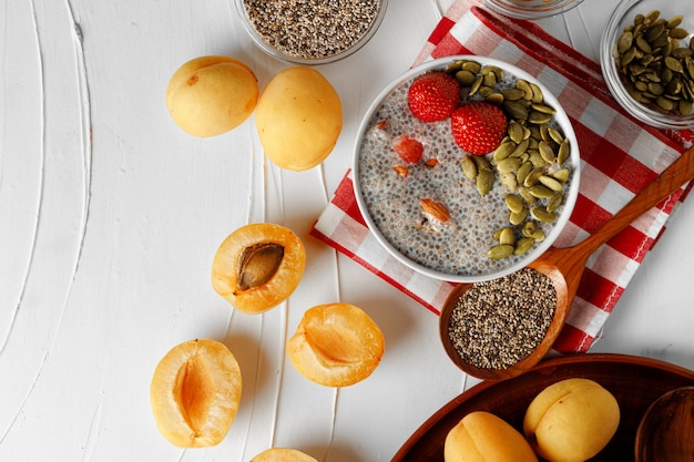 Пудинг из чиа с клубникой и семенами тыквы на деревянном столе с абрикосами