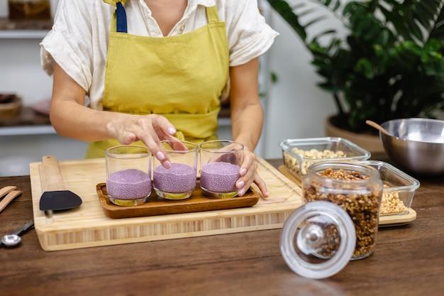 Processo di cottura dei budini di chia. latte di mandorle miscelato con estratto naturale di colore rosa frutto del drago e semi di chia.