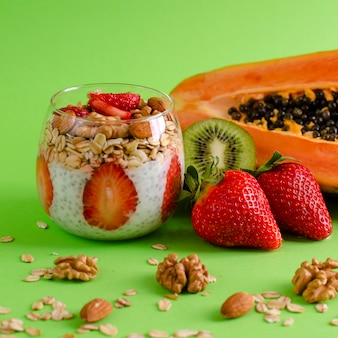 Chia puddings with fresh raw tropical fruits with oatmeals and nuts for healthy eating on green