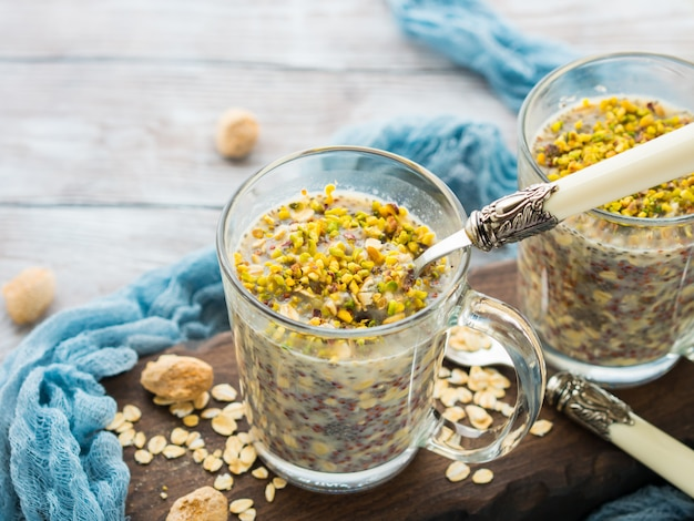 Chia rolled oat pudding overnight porridge with quinoa, banana, pistachio nuts, milk. one cup healthy breakfast