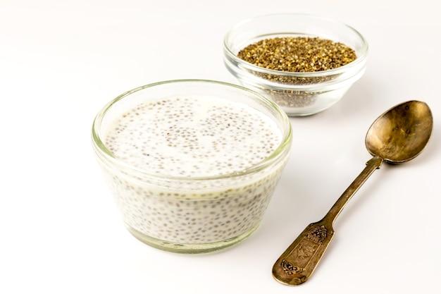 チアシードミルクプディングとビンテージスプーン付きの小さなガラスのボウルに乾燥した種子。閉じる。選択的なソフトフォーカス。テキストコピースペース。