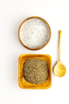 Chia seed milk pudding and dry seeds in bamboo bowls with wooden rustic spoon. top view. flat lay. close up. selective soft focus.  text copy space.