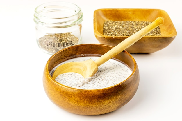 Chia seed milk pudding and dry seeds in bamboo and glass bowls with wooden rustic spoon. close up. selective soft focus.  text copy space.