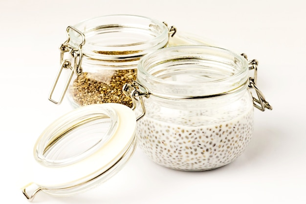 Chia seed milk pudding and dry seeds in glass jars. close up. selective soft focus.  text copy space.