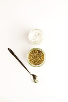 Chia seed milk pudding and dry seeds in small glass bowls with modern spoon. top view. flat lay. close up. selective soft focus.  text copy space.