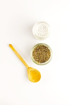 Chia seed milk pudding and dry seeds in small glass bowls with wooden rustic spoon. top view. flat lay. close up. selective soft focus.  text copy space.