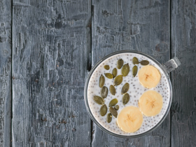 Chia seed pudding with banana and pumpkin seed on a dark wooden table. the view from the top. flat lay.
