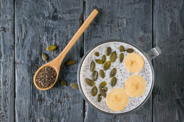 Chia seed pudding with banana and wooden spoon on dark wooden table. the view from the top. flat lay.