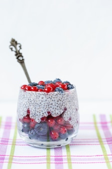 Chia seed pudding with blueberries and red currant berries in a glass