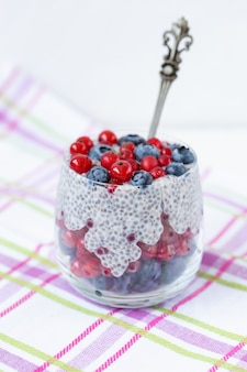 Chia seed pudding with fresh blueberries, red currant berries in a glass with spoon. superfood and vegan food concept. copy space.