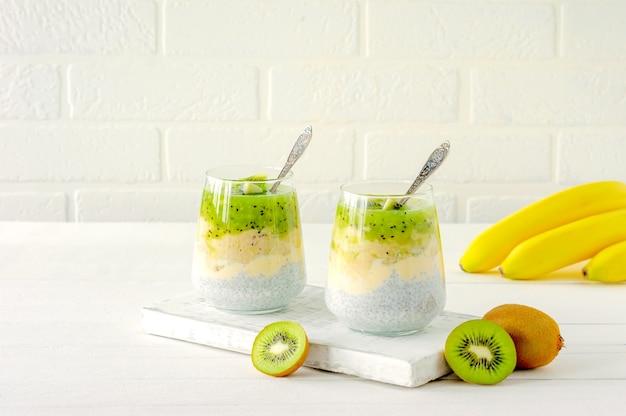キウイ、バナナ、マンゴーを使ったチアシードプリン。白い背景の上のメガネで健康デトックス朝食。