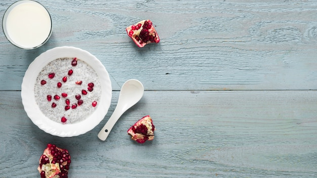 Chia seed pudding with seeds of pomegranate in white bowl with spoon
